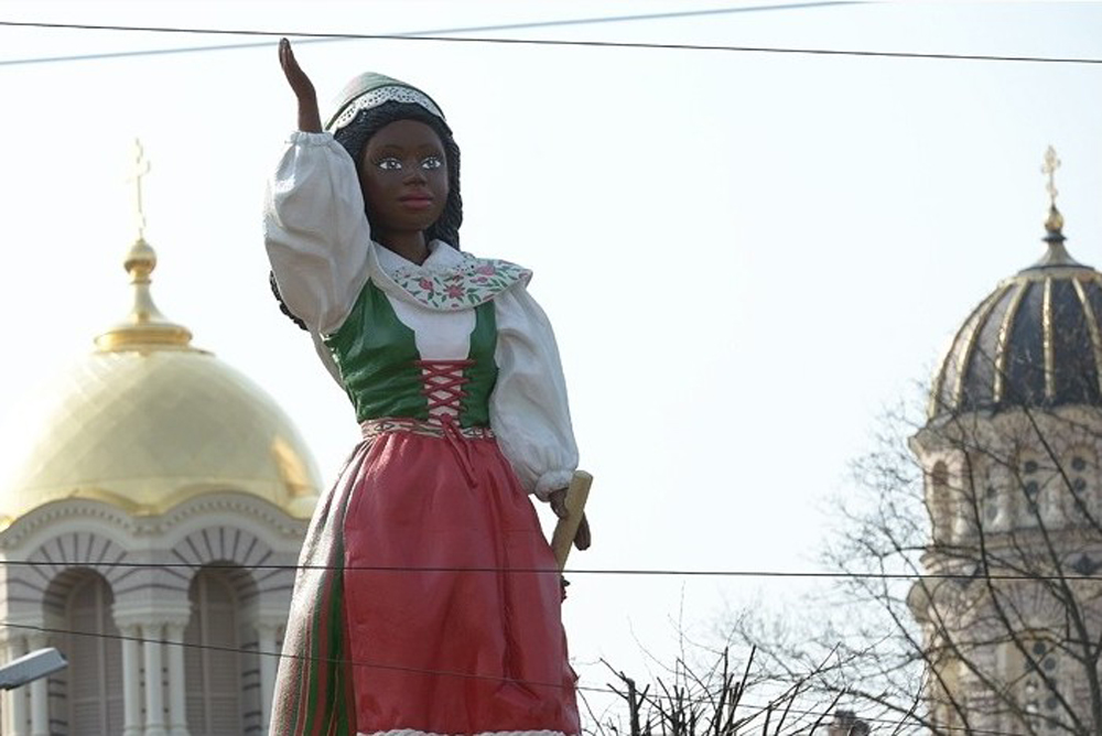 The black barbie dressed up as a Swedish maiden is one of the figure emerging from the box. Credit: Mārtiņš Otto, Rīga 2014.